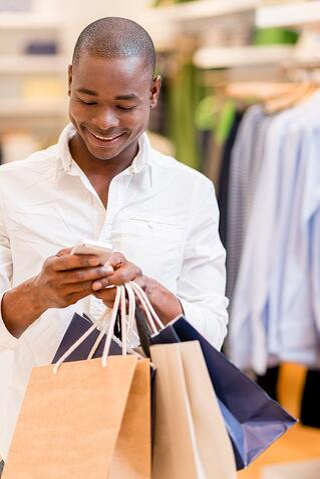 Shopping man texting on his phone at a store .jpeg