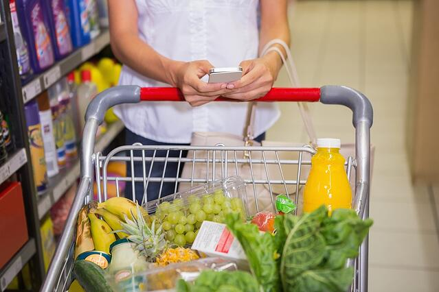 woman buy products and texting at supermarket.jpeg